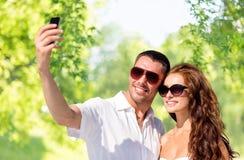 做selfie的微笑的夫妇由智能手机 免版税库存图片