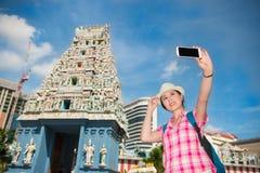 做selfie的微笑的少妇在Sri Mariamman寺庙,新加坡附近 免版税库存照片