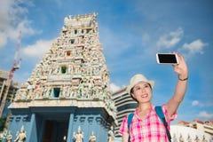 做selfie的微笑的少妇在Sri Mariamman寺庙,新加坡附近 免版税库存图片
