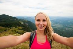 做selfie的愉快的妇女在绿色山谷上的一座山顶部 免版税库存图片