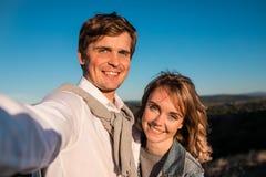 做selfie的愉快的年轻逗人喜爱的夫妇户外 免版税图库摄影
