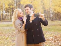 做selfie的愉快的微笑的年轻夫妇画象在smarphone 库存图片