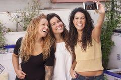 做selfie的愉快的最好的朋友在有a的流动或巧妙的电话 免版税图库摄影