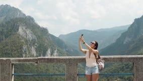 做Selfie的旅游女孩由桥梁Djurdjevic的电话在黑山,旅行生活方式 免版税图库摄影