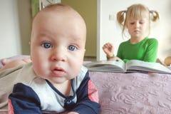 做selfie的沉思矮小的婴儿男孩画象在床 姐妹在背景的阅读书 浓缩的年龄的不同的兴趣 库存图片