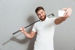 做selfie的滑稽的愉快的高尔夫球运动员在他的智能手机 免版税库存照片