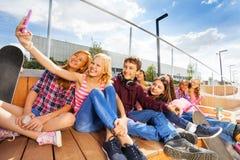 做selfie的白肤金发的女孩她和朋友 免版税图库摄影