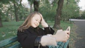 做selfie的美丽的女孩坐一条长凳在公园 股票视频