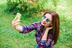 做selfie的美丽的时髦的妇女在公园 拷贝空间 免版税库存照片