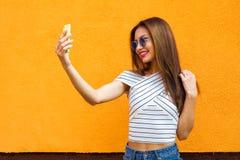 做selfie的美丽的时髦的妇女 橙色背景 拷贝空间 库存照片