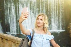 做selfie的美丽的白肤金发的女孩在瀑布的背景 她旅行并且获得乐趣 免版税图库摄影