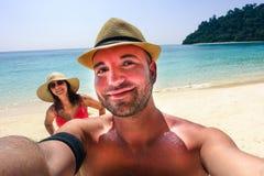 做selfie的英俊的行家夫妇在天堂海滩 免版税库存图片