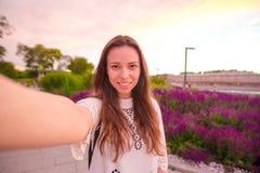 做selfie的年轻白种人妇女在吸引力背景户外在晚上光 库存图片