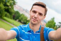 做selfie背景欧洲老城市的年轻白种人人由手机由观察地方 免版税图库摄影