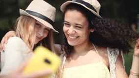 做selfies的两个快乐的女孩由湖 免版税库存照片