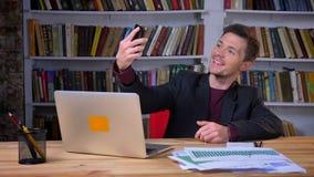 做selfies的可爱的男生在坐在膝上型计算机前面的电话在图书馆里户内 股票视频
