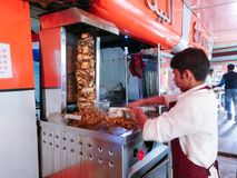 做shwarma的印地安人在一个老纵型烤架在路旁商店 库存图片