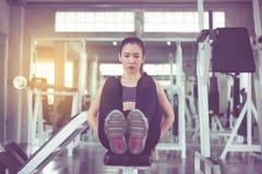 做situp或咬嚼在健身房的美丽的亚裔妇女,肌肉女性的锻炼她的胃 库存图片