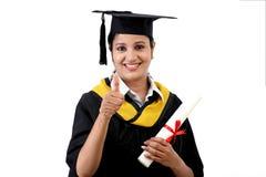 做thumbsup姿态的微笑的年轻毕业学生 库存照片