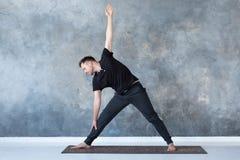 做trikonasana姿势的人初学者实践的瑜伽 免版税库存图片
