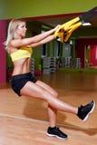 做TRX锻炼的美丽的少妇 库存图片