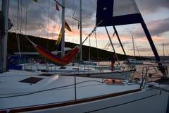 停住在海湾的三条游艇在日落 免版税库存图片