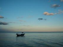 停住在海的渔船近由在日落的海滩 免版税库存照片