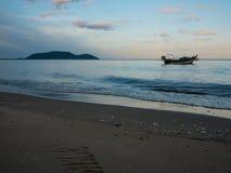 停住在海的渔船近由在日落的海滩 库存照片
