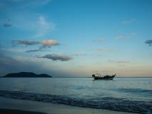 停住在海的渔船近由在日落no5的海滩有山背景 免版税库存图片