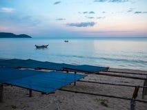 停住在海的渔船近由在日落no6的海滩,与接合板前景 图库摄影