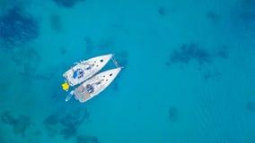 停住在礁石旁边的两艘帆船鸟瞰图  免版税库存图片