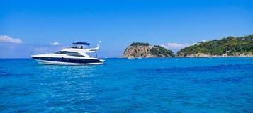 停住在陡峭的海岸的豪华游艇 免版税库存照片
