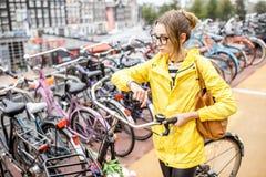 停放一辆自行车的妇女在阿姆斯特丹 免版税图库摄影