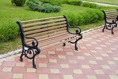 停放与棕色长凳和铺磁砖的背景的风景 免版税库存照片