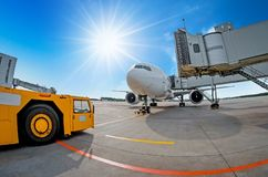 停放在机场,飞机在teletrap 机场拖拉机准备好航空器的拖曳和离开 反对 免版税库存照片