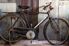 停放在生锈的波纹状的镀锌铁墙壁前面的葡萄酒自行车 库存图片