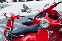 停放在街道上的红色滑行车 免版税库存图片