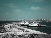 停放在Qaitbay城堡的墙壁的旁边两条大鱼小船在Alexanderia,埃及海岸的  免版税库存图片