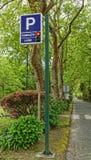 停放的交通标志和有红绿灯的有偿的停车区 免版税库存照片