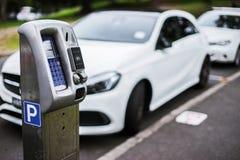 停放的机器或停车时间计时器有电子付款的在城市街道 库存图片