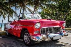 停放的红色葡萄酒汽车在海滩附近的哈瓦那古巴 免版税图库摄影