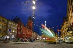 停放的自行车、街灯&红色巴塞尔城镇厅Marktplatz的在夜间期间与移动的绿色电车选定的轨道的 免版税库存图片