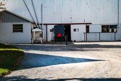 停放的门诺派中的严紧派的多虫的近的白色谷仓 免版税库存照片