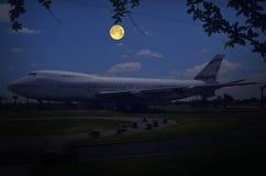 停放的飞机在有满月的公园 图库摄影