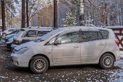 停放第一座雪秋天山的汽车 库存照片