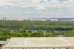 停机坪看法在一个大厦的屋顶的在一个城市公园有在背景的全景大都会视图 免版税库存照片