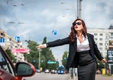 停止与赞许的街道的俏丽的女孩运输 免版税库存照片