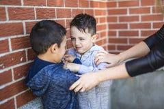 停止两个男孩的老师战斗在操场 图库摄影