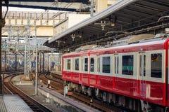 停止在京都驻地,日本的红色火车 免版税库存图片