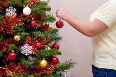 停止在圣诞树的妇女一baubel 库存照片